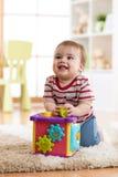 使用与整理者玩具的小小孩在家坐软的地毯 免版税库存图片