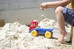 使用与他的卡车玩具的男孩在海滩沙子 图库摄影