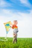 使用与他的在一个绿色领域的风筝的年轻男孩 免版税库存图片