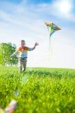使用与他的在一个绿色领域的风筝的年轻男孩 免版税图库摄影