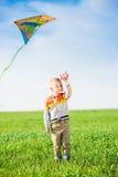 使用与他的在一个绿色领域的风筝的年轻男孩 免版税库存照片