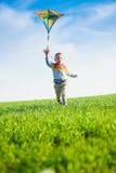 使用与他的在一个绿色领域的风筝的年轻男孩 库存照片