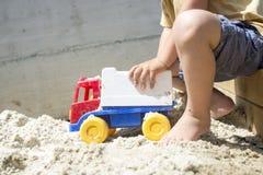 使用与他的在白色沙子的塑料卡车玩具的年轻男孩 免版税库存照片
