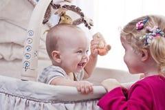 使用与他的姐妹的愉快的男婴 免版税库存图片