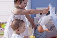 使用与他的姐妹的男婴在玩具室 免版税库存照片