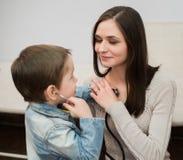 使用与他的母亲的小医生男孩听她的胸口使用听诊器 库存照片
