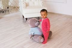 使用与他的玩具熊的愉快的男婴 免版税库存照片