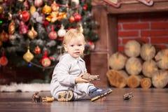 使用与他的玩具的小男孩由圣诞树 免版税库存照片