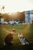 使用与滑稽的多壳的狗的美丽的少妇户外在公园在日落或日出 免版税图库摄影