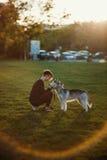 使用与滑稽的多壳的狗的美丽的少妇户外在公园在日落或日出 免版税库存照片