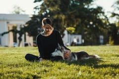 使用与滑稽的多壳的狗的美丽的少妇户外在公园 库存图片