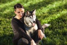 使用与滑稽的多壳的狗的美丽的少妇户外在公园 免版税库存照片