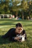 使用与滑稽的多壳的狗的美丽的少妇户外在公园 库存照片