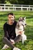 使用与滑稽的多壳的狗的美丽的少妇户外在公园 免版税库存图片