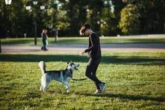 使用与滑稽的多壳的狗的美丽的少妇户外在公园 免版税图库摄影