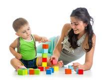 使用与建筑集合玩具一起的小男孩和母亲 免版税库存照片