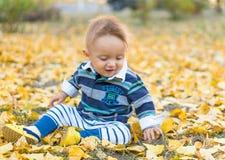 使用与黄色的小男婴在公园离开 免版税图库摄影