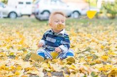 使用与黄色的小男婴在公园离开 图库摄影