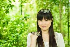 使用与蝴蝶的愉快的女孩在庭院里 免版税库存图片