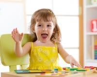 使用与逻辑玩具的小女孩孩子 排序和安排颜色和形式的孩子 免版税库存图片