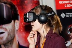 使用与Homido在机器人学商展的虚拟现实耳机的女孩在莫斯科,俄罗斯 库存照片