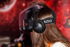 使用与Homido在机器人学商展的虚拟现实耳机的女孩在莫斯科,俄罗斯 库存图片