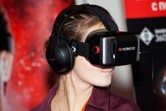 使用与Homido在机器人学商展的虚拟现实耳机的女孩在莫斯科,俄罗斯 免版税库存图片