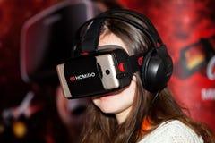 使用与Homido在机器人学商展的虚拟现实耳机的女孩在莫斯科,俄罗斯 免版税图库摄影