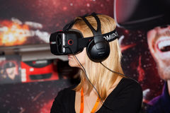 使用与Homido在机器人学商展的虚拟现实耳机的女孩在莫斯科,俄罗斯 免版税库存照片