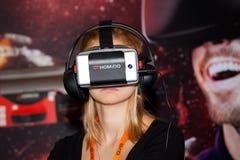 使用与Homido在机器人学商展的虚拟现实耳机的女孩在莫斯科,俄罗斯 图库摄影