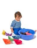使用与origami纸张船的一个小的小女孩 免版税库存照片