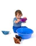 使用与origami纸张船的一个小的小女孩 免版税库存图片