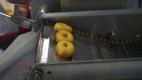 使用专业厨房钳子的一位厨师在客户的一个箱子采取在多福饼机器烹调的油炸圈饼并且投入他们 影视素材