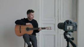 使用专业照相机,年轻俏丽的音乐家博客作者记录关于弹吉他的讲解互联网博克的 ? 股票录像