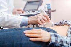 使用专业设备的纯熟医生在超生波检查法内阁 库存图片