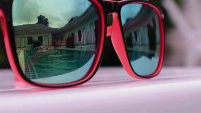 使用两个少年的女孩,游泳和享受在后院水池的太阳` s光芒 海滩蓝色反映太阳镜水 股票视频