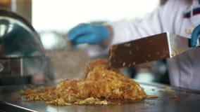 使用两种金属小铲,橡胶手套的厨师混合在火炉的菜 股票视频
