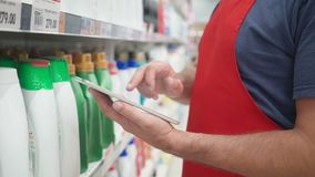 使用个人计算机片剂的推销员手在擦净剂前面在现代杂货零售店搁置 股票录像