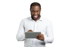 使用个人计算机片剂的兴高采烈的商人 库存照片