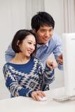 使用个人计算机的新亚洲夫妇 库存照片