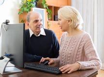 使用个人计算机的资深夫妇在家 库存照片