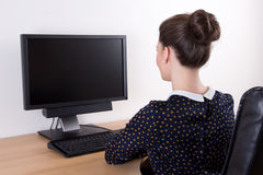使用个人计算机以空的后面观点的年轻美丽的女商人 免版税库存照片