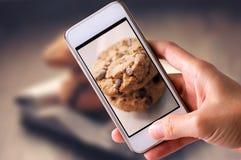 使用为的手机在木背景的巧克力曲奇饼照相 库存照片