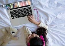 使用书架的孩子在膝上型计算机屏幕上 库存照片