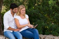 使用互联网的夫妇室外与数字式片剂 图库摄影