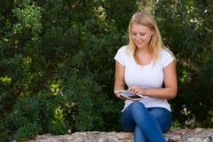 使用互联网的少年室外在公园 免版税库存照片