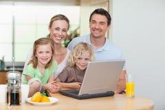 使用互联网的微笑的家庭在厨房里 库存图片