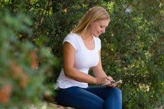 使用互联网的白肤金发的少妇室外 库存图片