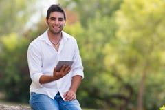 使用互联网的年轻人室外在公园 免版税库存照片