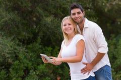 使用互联网的年轻夫妇室外与数字式片剂 图库摄影